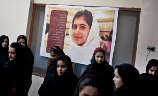 Pakistani school children gather under a poster of Malala at the Khushal School for Girls in Swat Valley Pakistan on November 15, 2012.