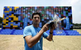 Illac Diaz displays a recycled plastic mineral water container equipped with an inexpensive solar powered bulb that can be used to light homes for as long as five hours. (AP Photo/Bullit Marquez)