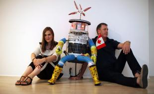 HitchBOT poses with her co-creators Frauke Zeller, an assistant professor at Ryerson University, and David Smith, a professor in the department of communication studies at McMaster University in Victoria, B.C., on Thursday August 21, 2014. (THE CANADIAN PRESS/Chad Hipolito)