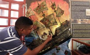 A man points to an illustration of the Spanish galleon San Jose during a press conference to announce the finding of the shipwreck near Cartagena, Colombia, in December. [Photo courtesy EPA/RICARDO MALDONADO ROZO.]