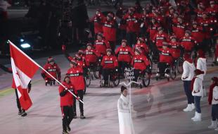 Brian McKeever carries Canada's flag as he leads his teammates into the opening ceremony of the 2018 Winter Paralympics in PyeongChang, South Korea, on March 9, 2018. (AP Photo/Ng Han Guan)
